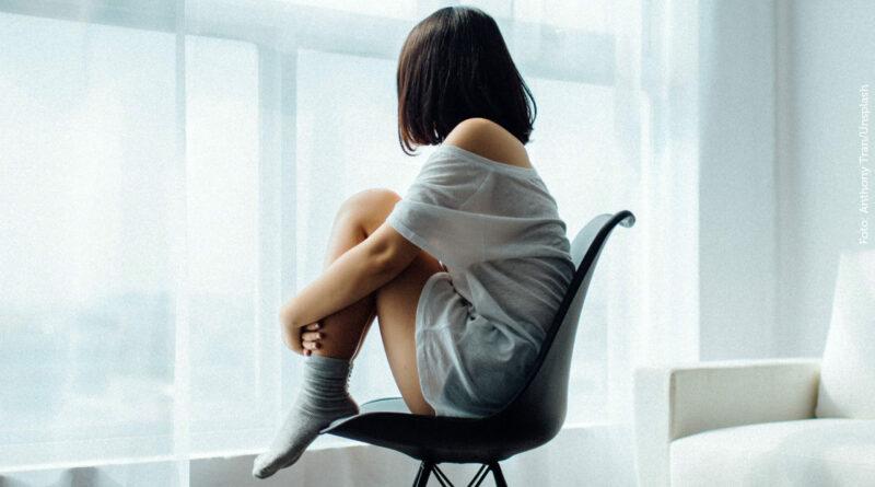 Eine junge Frau sitzt einsam auf einem Stuhl und schaut durch das Fenster, Vorhänge verdecken die Sicht an Außen. (Foto: Anthony Tran/unsplash)